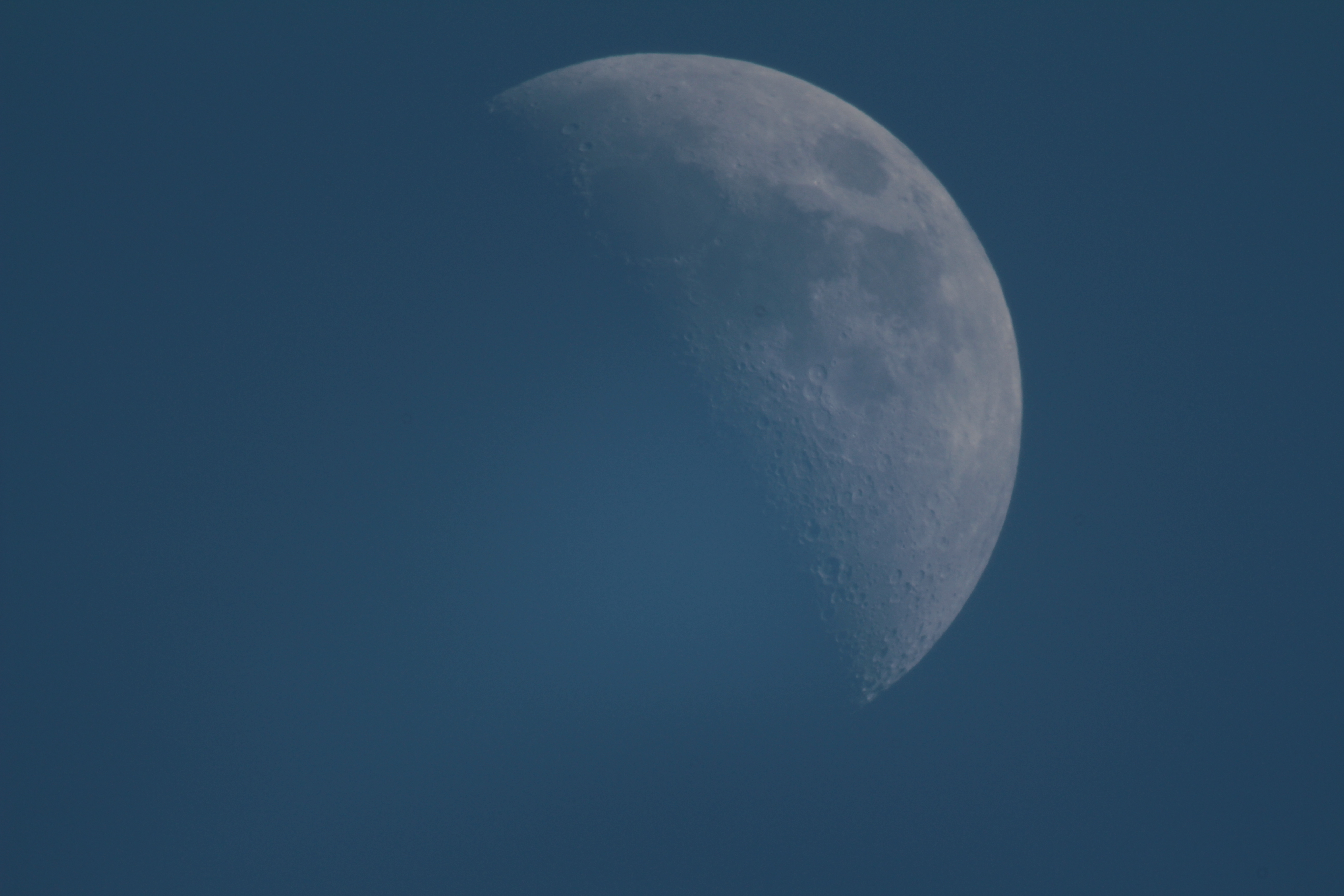 Image: A picture of the half-moon on a blue sky background.